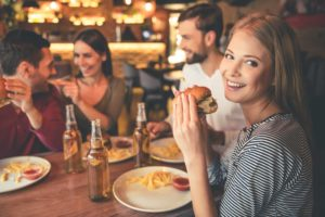 woman eating burger, friends eating at restaurant