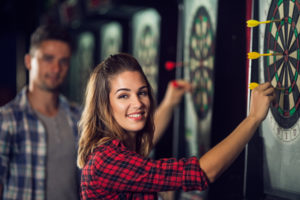 couple playing darts at bar